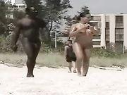 Femme nue avec un homme noir nu filmé à la plage