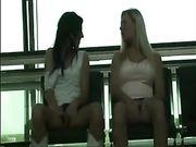 Deux jeunes filles se touchent dans un lieu public