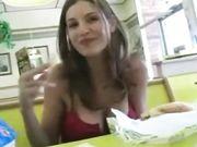 Une fille mignonne montre seins et la chatte dans un restaurant public