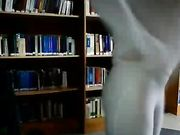 Une jeune fille est nue dans une bibliothèque publique