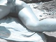 Doigt dans le cul de la femme à la plage nudiste